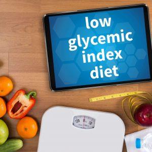 wyświetlony na tablecie napis low glycemic index diet, pod spodem warzywa, waga oraz metr krawiecki