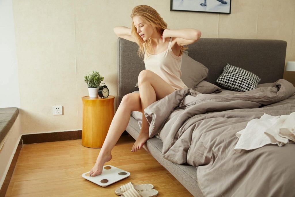 kobieta staje na wagę po wyjściu z łóżka