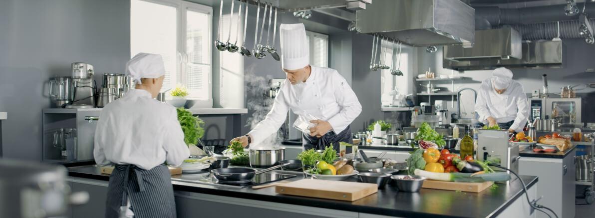 widok na kuchnię, trzech kucharzy pracuje pośród palników, przyborów kuchennych i warzyw